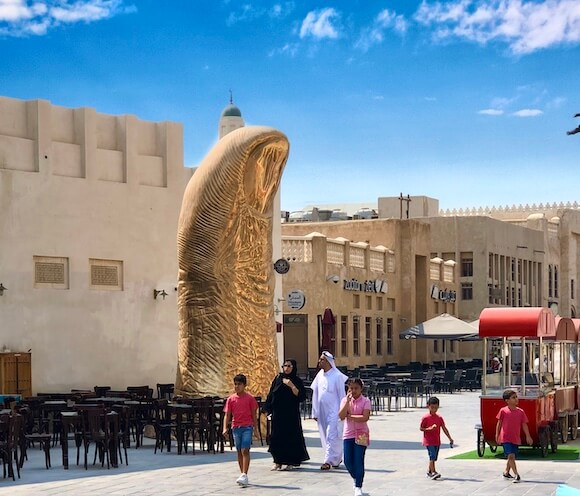 people walking in square with giant thumb sculpture
