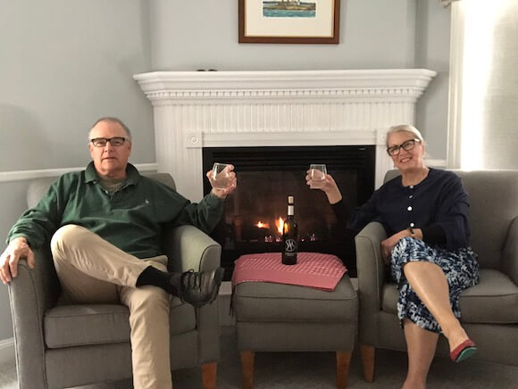 Couple sitting by fireplace at Inn at Oceans Edge