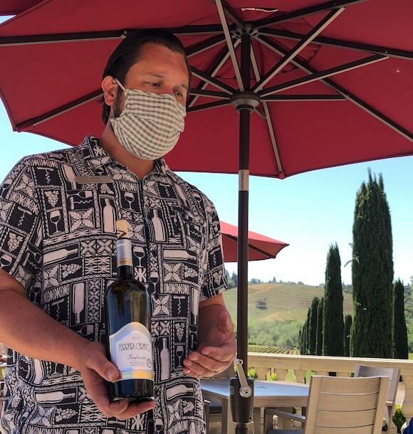 man serving wine under umbrella
