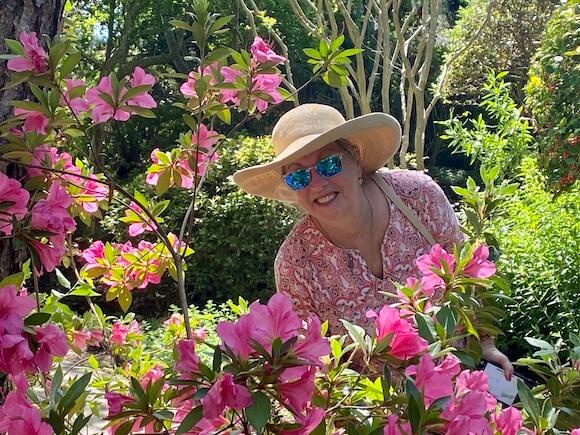 woman in garden of pink azaleas