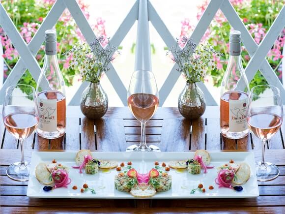 rosé and snacks on table