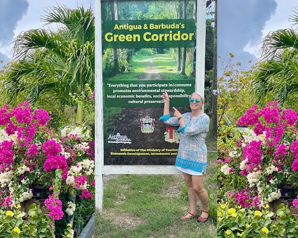 Woman pointing to sign and bougainvillea on each side.