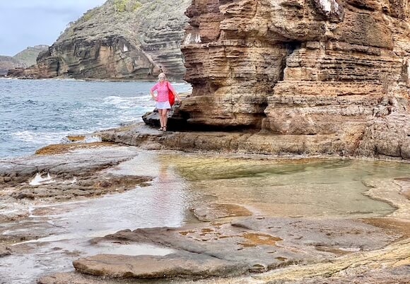 Woman standing near rocks and tide pools of water