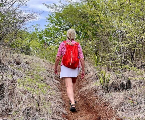 Woman hiking with orange backpack.