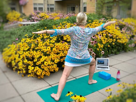 woman doing warrior pose in a garden looking at computer