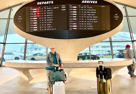 woman at TWA Hotel with suitcases